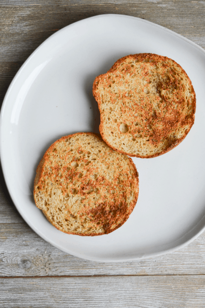 two toasted low carb bun halves sitting on a white plate