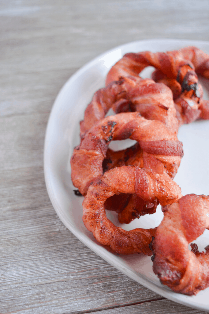 bacon wrapped onion rings on a white plate
