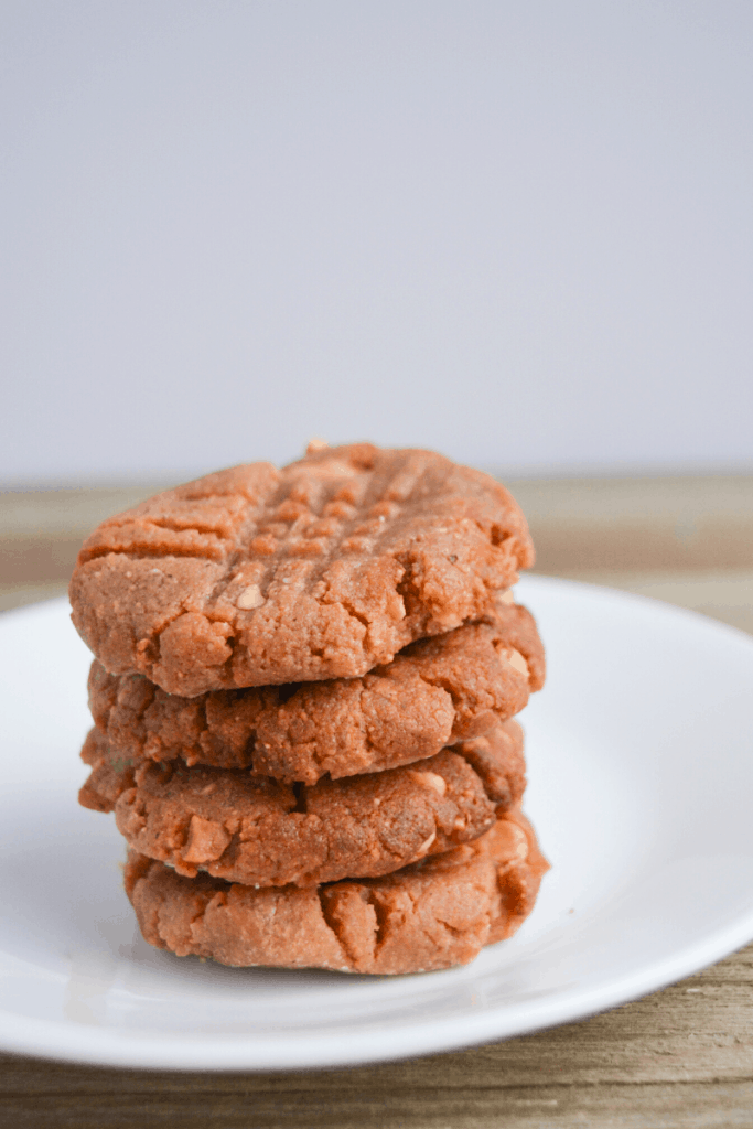 four peanut butter cookies stacked on a white plate