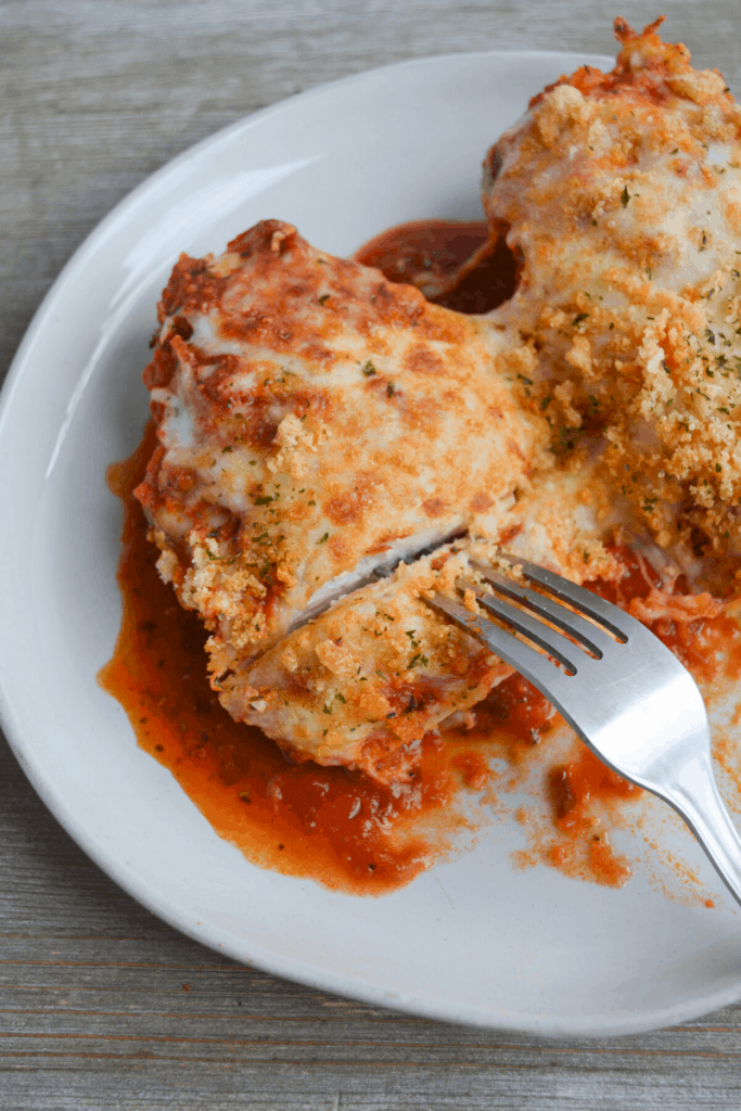 chicken parmesan on a white plate with a fork picking up a small piece