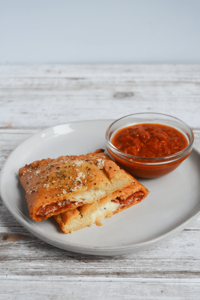 air fryer calzone, cut in half sitting on a white plate next to a dish of marinara sauce