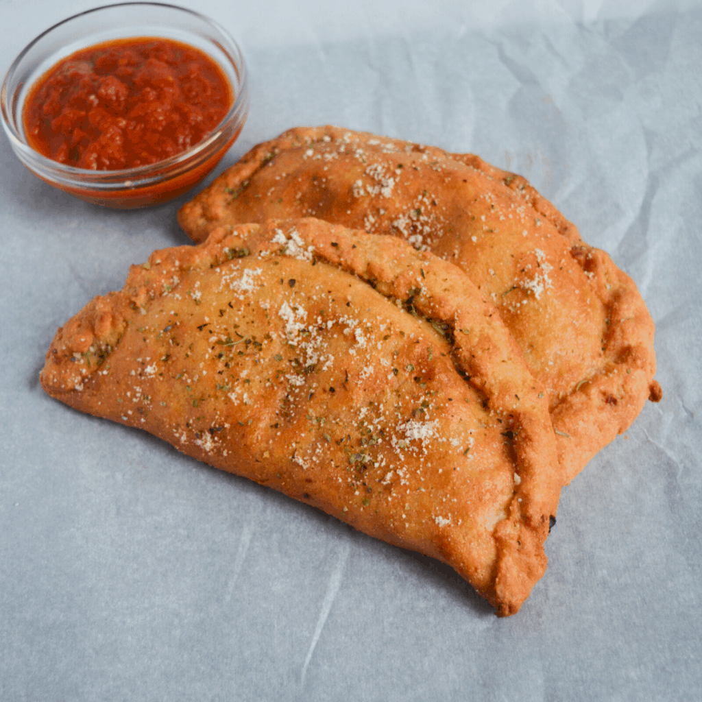 keto air fryer calzones on parchment paper sitting next to a small bowl of marinara sauce