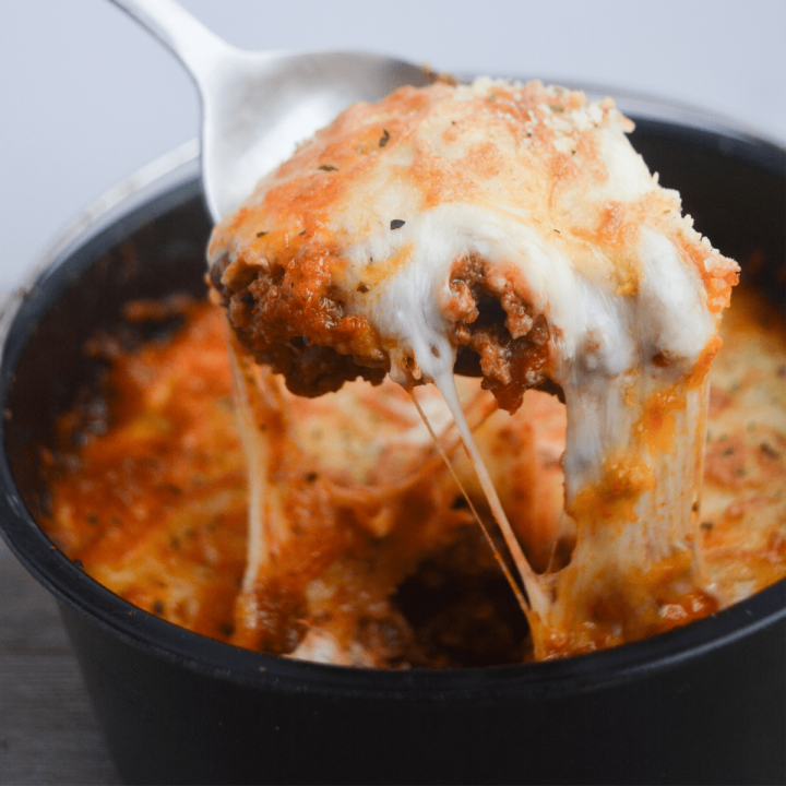 pan of keto lasagna with a spoon taking a scoop out of it