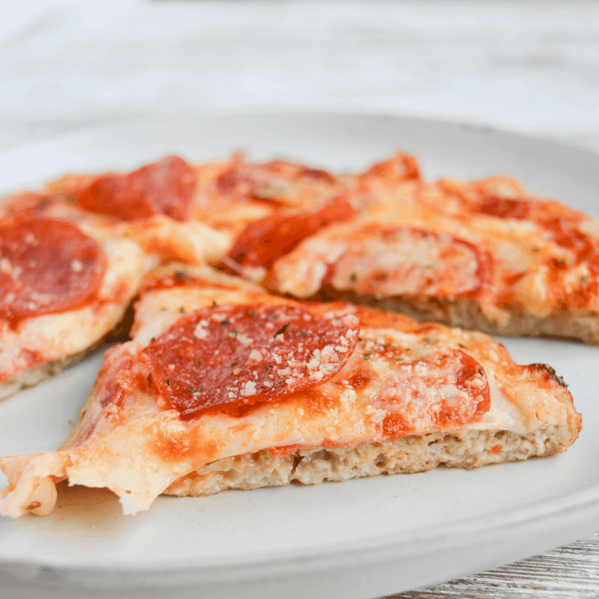 slice of air fryer chicken crust pizza, showing the texture of the crust