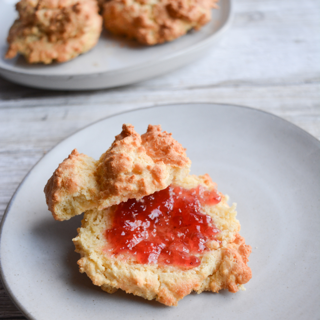 close of of a keto air fryer biscuit, cut in half and spread with strawberry jelly