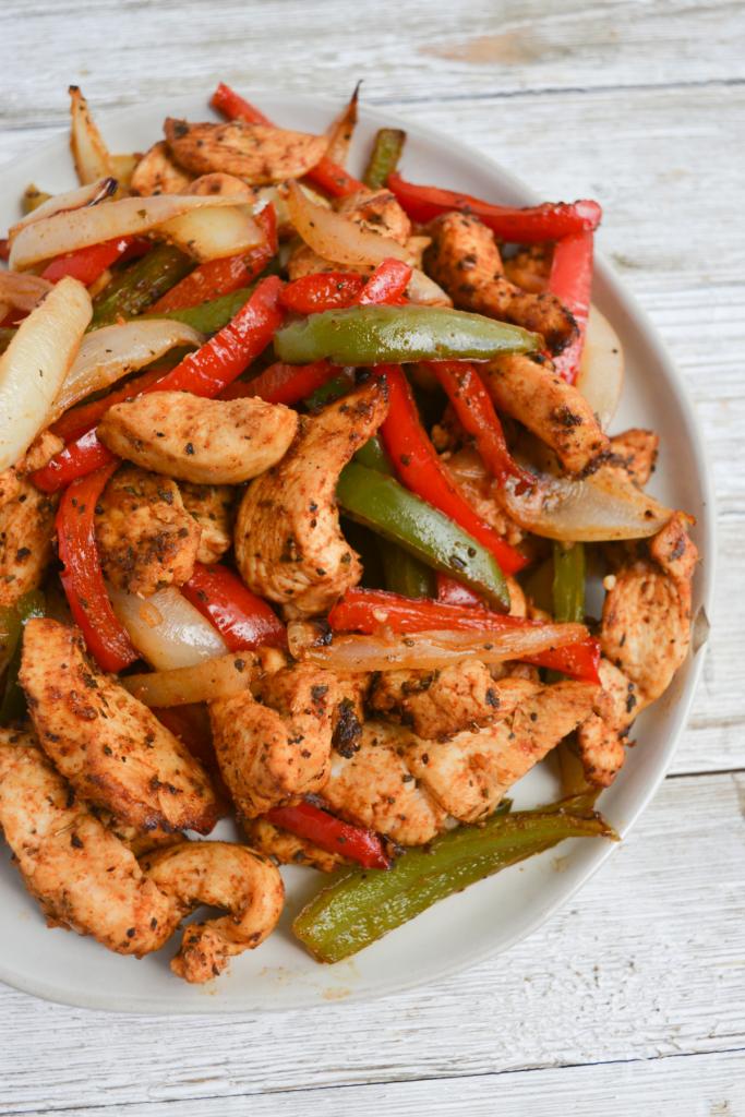 plate of air fryer chicken fajitas, including seasoned chicken breast, sliced green bell peppers, sliced red bell peppers, and sliced yellow onion